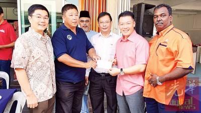 倪可敏移交捐款予人民社警代表宋修良,左起郑国霖、廖泰义和那拉陪见证。