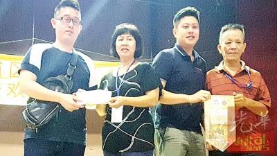 林振强及理事杨优琪移交捐款予中元联合会代表陈秋娟,钟少林回赠锦旗。