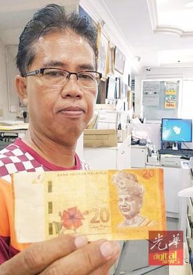 莫哈最后杰弗里著在夜间市场购物兑换到的20令吉伪钞。