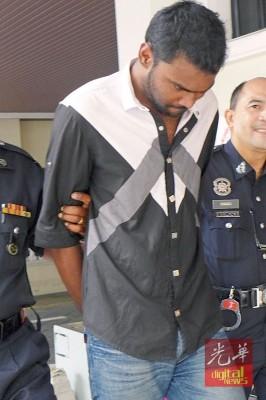 被告被押往法庭时,低头避开镜头。