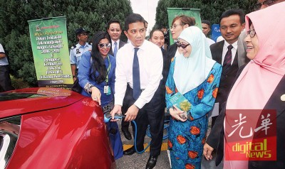 阿兹敏(前排左2)出席州议会之际,也与旺阿兹莎(前排右2)参观在议会厅外展览的电子车。