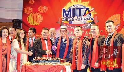 """纳兹里(中)配合主席身穿一席""""上海滩""""服装,与大马入境旅游协会12周年理事唱生日歌和切蛋糕。前排左起为钟玉霞、梁伟虹、乌再迪;右起为阿都哈里斯、亚当卡玛和欧阳羱瑱。"""