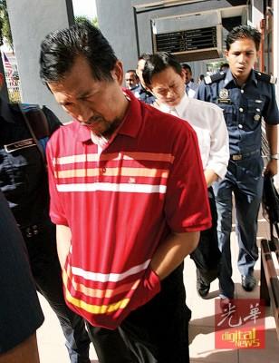 阿末再华威(前)与身后的莫兆俊(译音)涉嫌进项税诈骗,周一被带上法庭面控。
