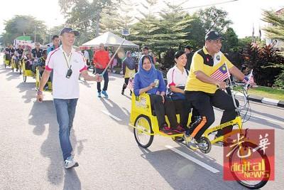 霹雳州秘书拿督斯里阿都布哈(前)负责驾驶黄包车,载送诺丽(坐者左起)及冯盈仪。