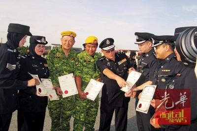 接领褒扬状的警员及志愿警卫团团员与岑振强(左5)合照。