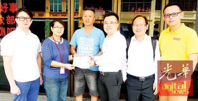 林道宏(右3)在钱庆顺见证下,移交4000令吉支票予光华市场有限公司副经理洪玉璇(左2),陪同者左起张顺华、执行秘书黄一豪和会员杨国雄。