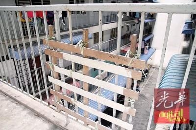 高楼铁制围栏已腐朽,居民暂以木垫取代。