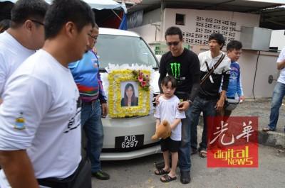死者丈夫与女儿在死者灵车离开家宅前合照。