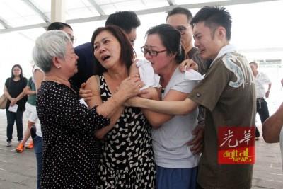 死者遗体焚化后,家属与亲友们抱在一起。