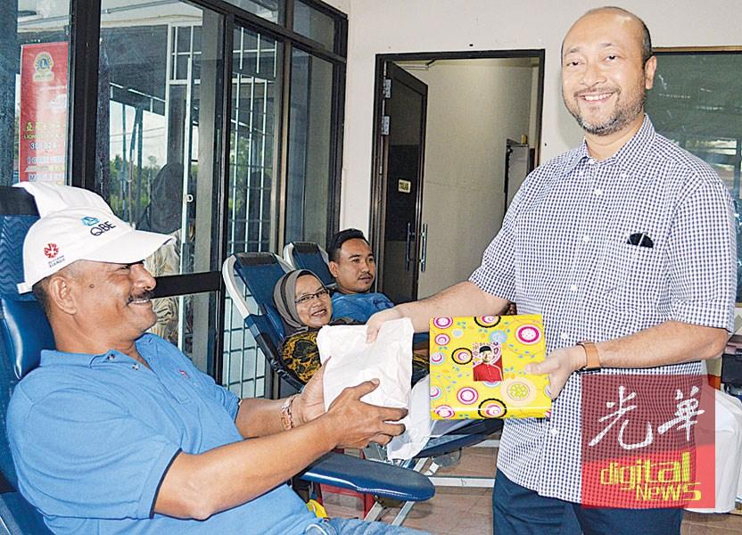 慕克里(右)移交礼品给予捐血者。