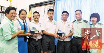 蔡慧琳(左2)与陈连龙(右3)将钱包交还张启业(左3)及王宗毅(右4),由校长陈秋梅(左)、教师莫淑敏(右起)及副校长王剑伟见证。
