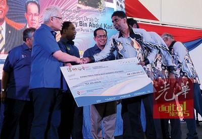 韩沙(左)移交贷款模型支票给怡保市政厅员工合作社,由代表接领。