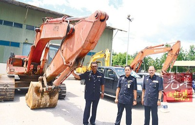 阿兹(左)展示起获的重型机械。