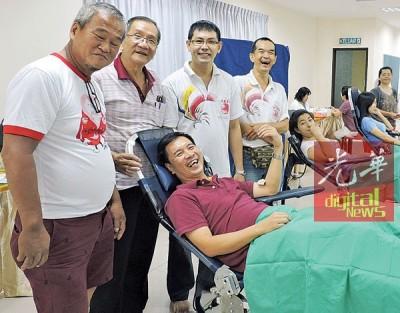 『爱心甘露』捐血活动联委会主席姜招丰首个响应捐血。后排左3为姜联兴。