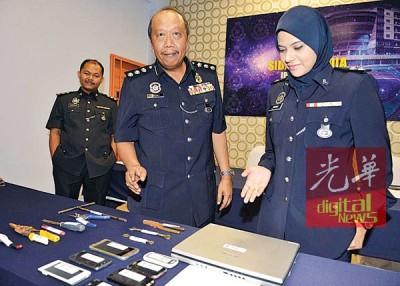 梅格(倍受)以及女性查案官展示起获的赃物和违法工具。