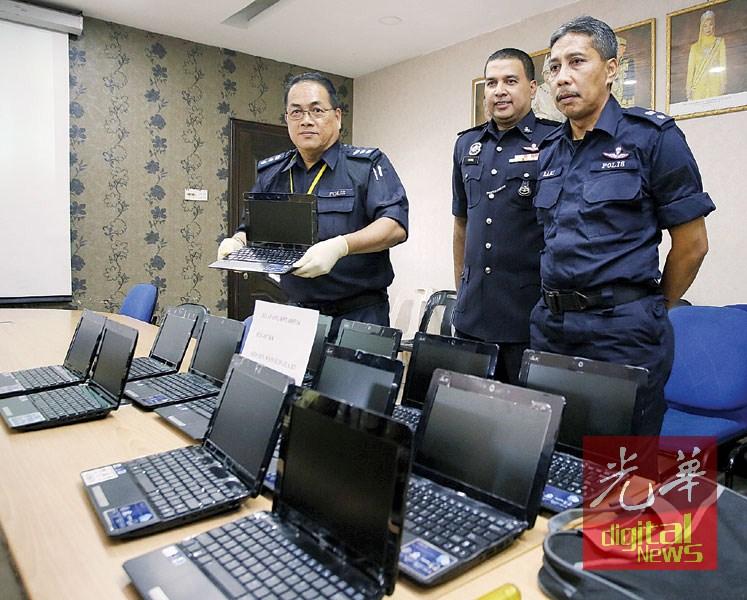 岑振强(左) 展示警方起回的手提电脑。右1起是拉尼及沙仑。