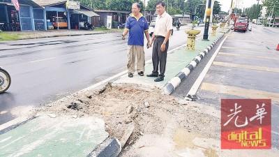 许福光(右)展示公共工程局在道路中间的水泥隔离墩,挖掉的部分,以作为排水道。
