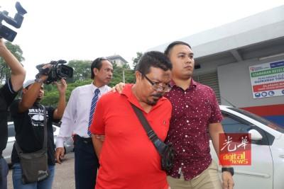 被告(红色汗衫者)周一被带往新山推事庭面控。