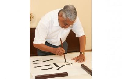 """纳丹在总统府练习书法,写的是""""仁心""""两个字。(档案照)"""