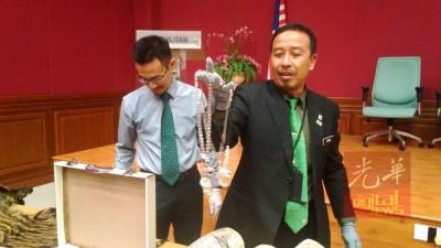 阿都卡迪(右)当记者会后,朝记者出示其中一个为制成项链的动物装饰物。左是罗兹丹。