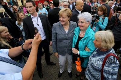 德国总理默克尔(中)上周六为地方选举拉票,与支持者合照。
