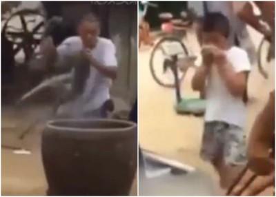 男子把活狗掉入一缸沸水中,目击过程的男童(右)一脸惊恐。
