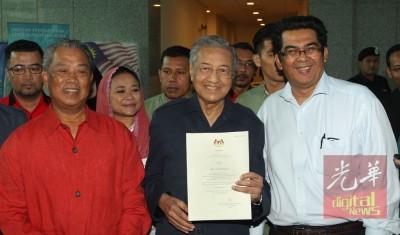 马哈迪(中)向媒体展示刚获得注册土团党的证书。左为慕尤丁。