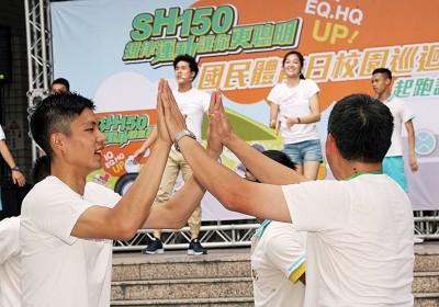 周天成(左)在艺人李博翔和邱子芯(舞台上)示范下,与师长及学弟妹们一起做健身操。