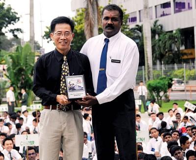 槟城圣芳济中学代校长巴拉桑德兰(右)在陈锦兴荣休仪式上赠送纪念品给后者,感谢陈锦兴在教育和本地羽球运动上的贡献。