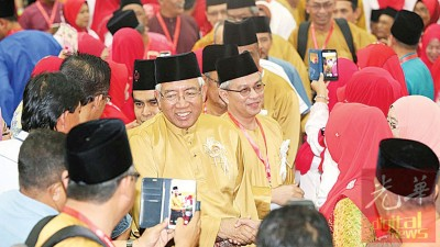 马哈兹尔(面向镜头左)到会场,受党员们的利害欢迎。