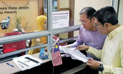 沈志勤(右)跟黄伟益曾于周四(15天)交槟选委会办公室,提出购买最新槟州总选民册的要求。