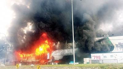 大火烧毁家具陈列中心,浓烟冒上半空。