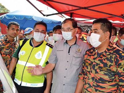 马汉顺(右2)在怡保警区主任岑振强(左2)的陪同下听取消拯局人员的汇报。