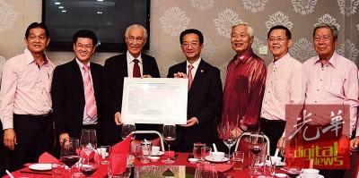 陈列凯希(左3)捐赠纪念品予黄惠康。左起为颜来发、陈列祈福、谢松坤、郑今智与黄仕美。