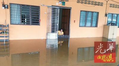 居民以木板试图挡在水量涌进屋内。