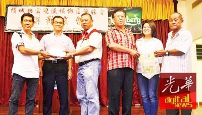 邝广良(左)移交款项给中元联合会代表黄天发(左3),陈国元(右)回送锦旗给李万强(右3),吴洑安(左2)和林秀琴(右2)见证。
