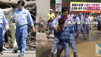 务台俊介本月一日到岩泉町视察时因无穿长靴,故要由随行人员背着他(右图)涉水而行,引来强烈批评。