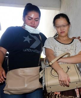 涉嫌毒死丈夫和儿女的女嫌犯(右)被警员扣查。