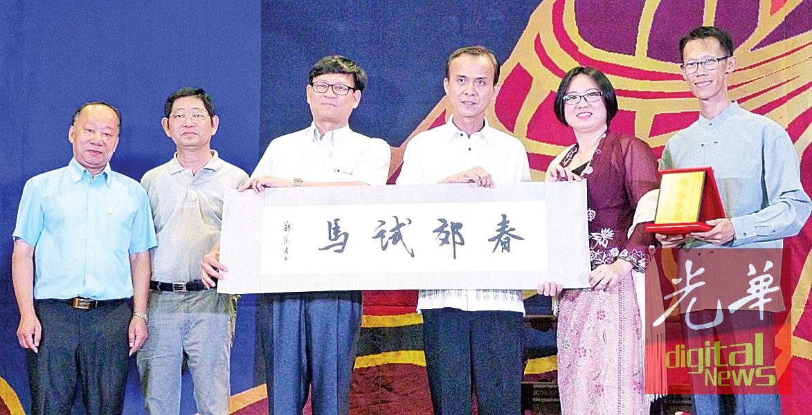 黄桂玲(左3)赠送墨宝给甲五邑会馆代表麦志坚。左起方炳焯、郑集思;右起张广权及梁雪玲。