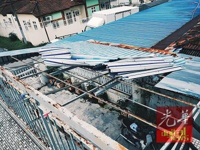 临到一半度的锌板屋顶遭掀起,似乎台风经过。
