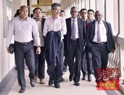 赛阿芬迪(左2)在支持者的陪同下,步抵法庭聆审。