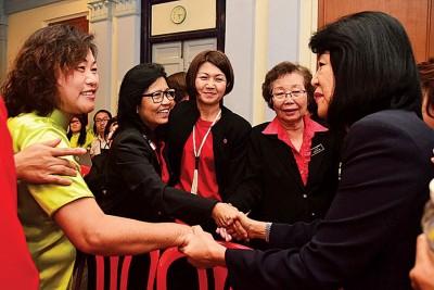 李玉花积极与黄玉珠握手,以示恭喜。