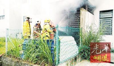 浓烟从厨房传出,消拯员利用水笔通过窗口射水。
