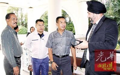 被告耶谷哈山(右2)与辩护律师潘吉星在庭外研究案情。