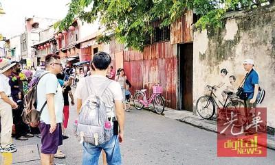打铜仔街的姐弟共骑壁画,吸引一些游客到访拍照留念。
