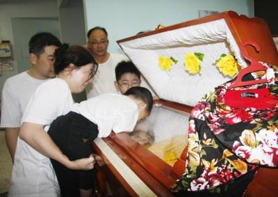 小骏昇伏在棺木上,隔着玻璃为奶奶献上最后一吻。