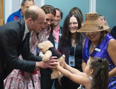 威廉王子夫妇抱小女孩送上泰迪熊。\=(法新社照片)