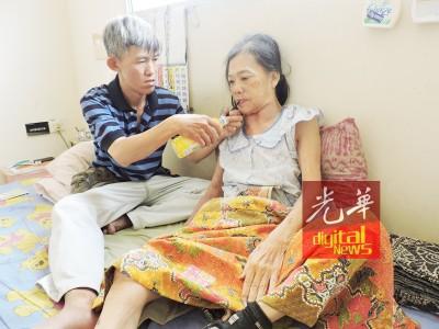 林金山喂骨折瘫痪的老母亲喝水。