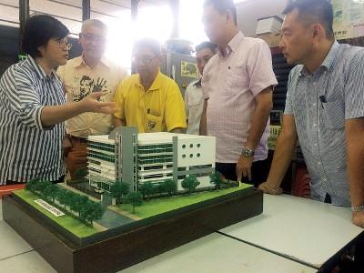 黄琮岚(左3)向周美芬(左)讲解关于峇东佛义综合医疗中心大厦,未装上自动洒水器的防火装备事项。