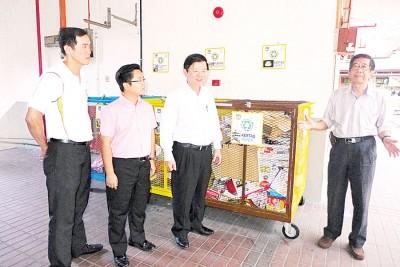 (右起)戴财福向曹观友、王宇航及陈明瑞讲解该组屋垃圾源头分类的方式。